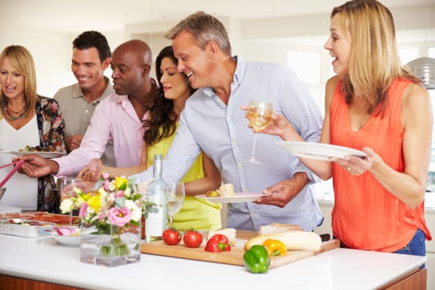 Plan a potluck dinner party to save money while spending time with friends